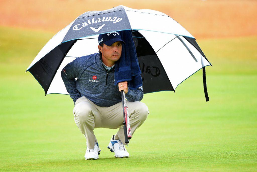 Der Regenschirm ist sehr nützlich während einer Runde Golf bei Regen. US-Golfer Kevin Kisner während Runde zwei bei der British Open 2015 im schottischen Royal Troon. Das Handtuch hänggt unter Schirm, der Schläger ist geschützt und eine Hand wird sogar noch in der Hosentasche warm und trocken gehalten. (Foto: Getty Images).