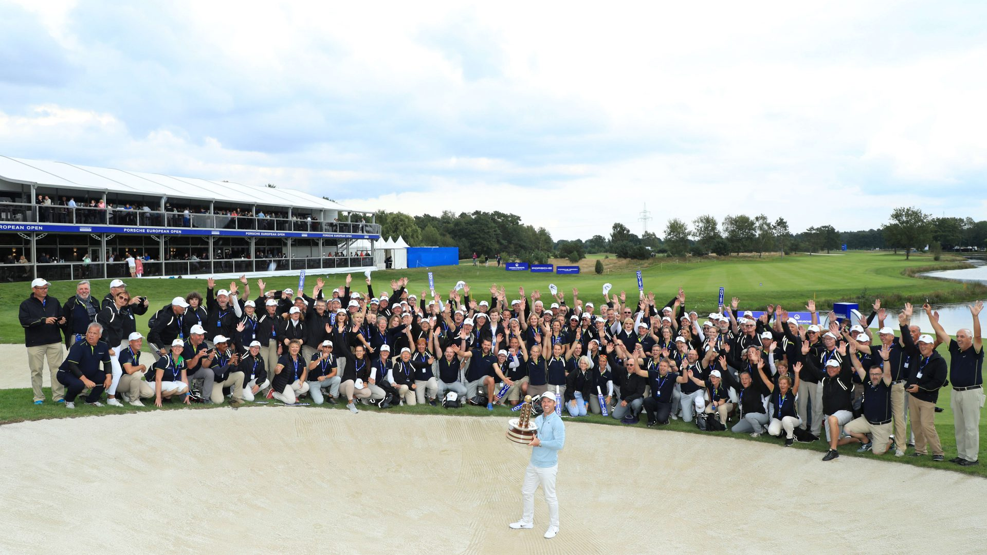 Paul Casey of England celebrates with the trophy in front of volunteers following Day 4 of the Porsche European Open at Green Eagle Golf Course on September 08, 2019 in Hamburg, Germany